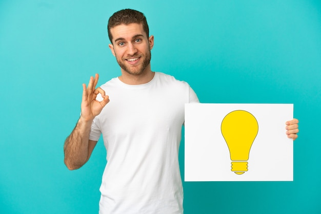 Handsome blonde man over isolated blue background holding a placard with bulb icon with ok sign