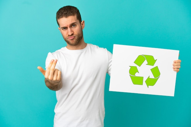 Handsome blonde man over isolated blue background holding a placard with recycle icon and doing coming gesture