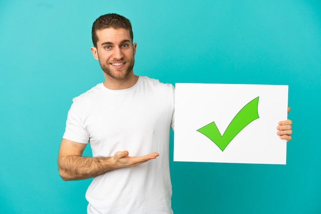 Handsome blonde man over isolated blue background holding a placard with text green check mark icon and  pointing it