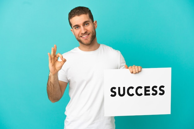Handsome blonde man over isolated blue background holding a placard with text success and celebrating a victory