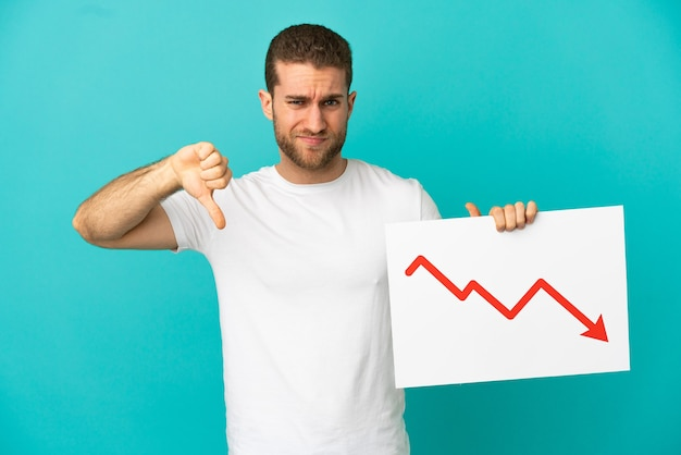 Handsome blonde man over isolated blue background holding a sign with a decreasing statistics arrow symbol and doing bad signal