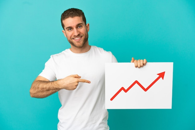 Handsome blonde man over isolated blue background holding a sign with a growing statistics arrow symbol and  pointing it