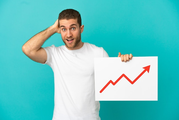 Handsome blonde man over isolated blue background holding a sign with a growing statistics arrow symbol with surprised expression