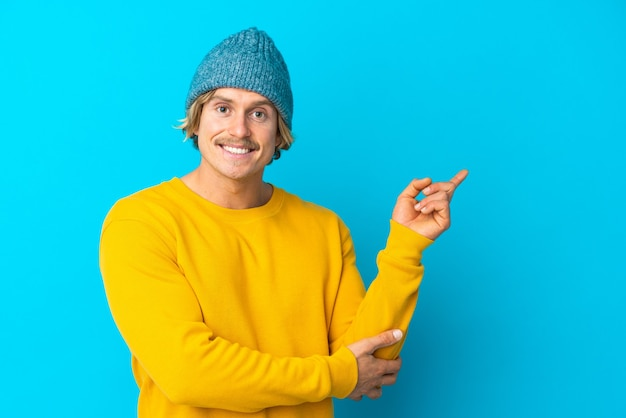 Handsome blonde man isolated on blue happy and pointing up