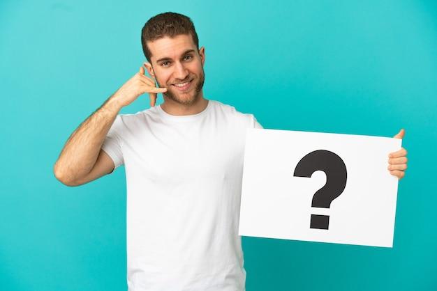 Красивый блондин изолирован, держа плакат с символом вопросительного знака и делая жест телефона