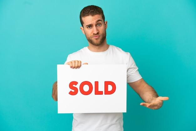 Красивый блондин изолирован, держа плакат с текстом продано и указывая на него