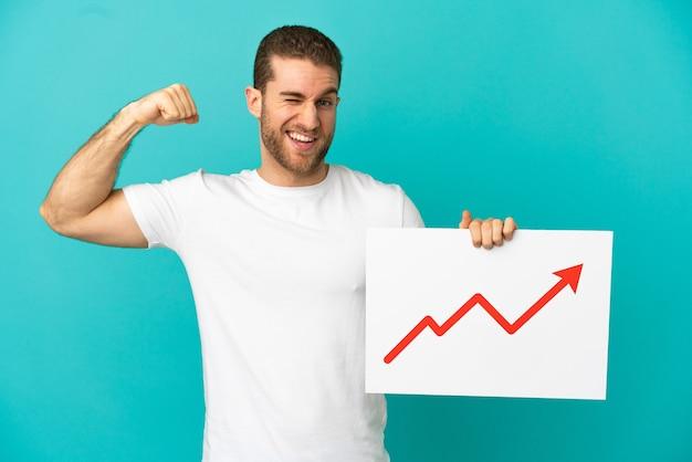 잘 생긴 금발의 남자는 성장 통계 화살표 기호로 기호를 들고 강한 제스처를하고 격리