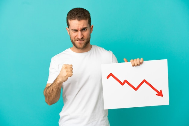 Handsome blonde man isolated holding a sign with a decreasing statistics arrow symbol and angry