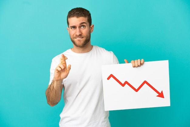 Handsome blonde man isolated holding a sign with a decreasing statistics arrow symbol with fingers crossing