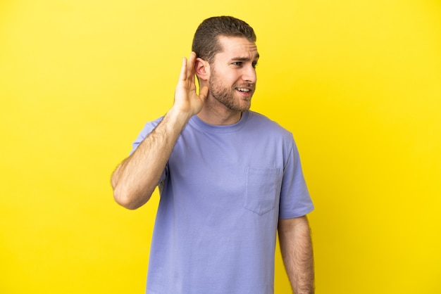 Handsome blonde man isolated listening to something by putting hand the ear