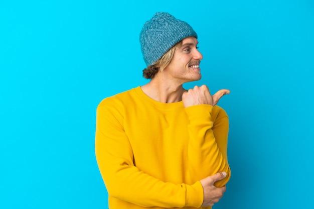 製品を提示する側を指している青い背景に分離されたハンサムなブロンドの男