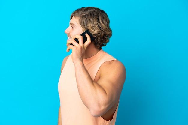 누군가와 휴대 전화로 대화를 유지하는 파란색 벽에 고립 된 잘 생긴 금발 남자