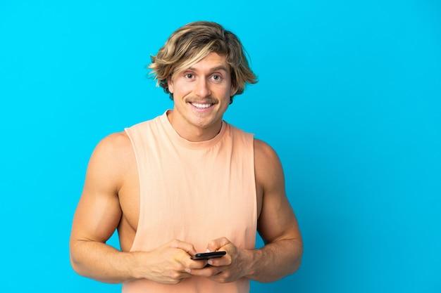 Красивый блондин, изолированный на синей стене, отправляет сообщение с мобильного телефона