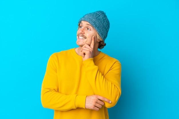 찾고있는 동안 아이디어를 생각하는 파란색 벽에 고립 된 잘 생긴 금발 남자