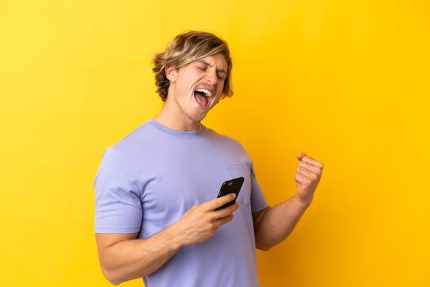 Красивый блондин, изолированные на желтом фоне с телефоном в позиции победы