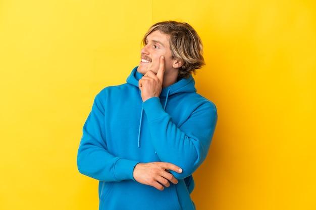찾고있는 동안 아이디어를 생각하는 노란색 벽에 고립 된 잘 생긴 금발 남자