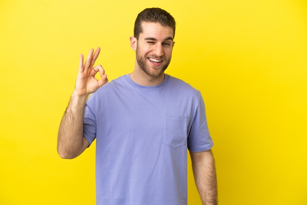 Красивый белокурый мужчина изолирован, показывая знак ок пальцами