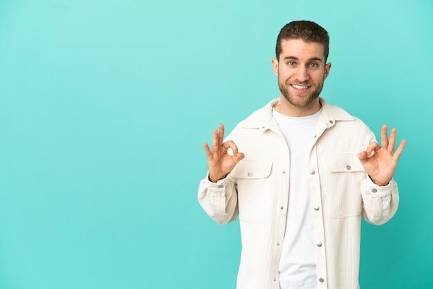 Красивый белокурый мужчина изолирован, показывая знак ок двумя руками