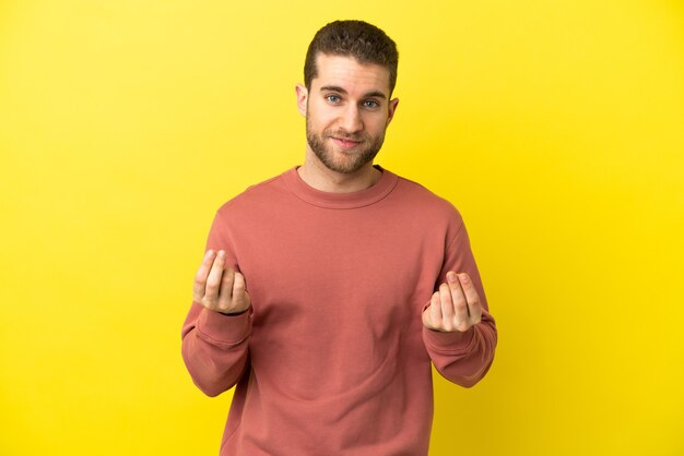 Handsome blonde man over isolated yellow background making money gesture