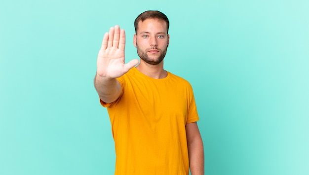 Handsome blonde man looking serious showing open palm making stop gesture