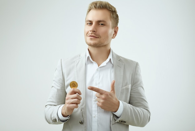 Handsome blonde man model in a fashion gray suit holds a bitcoin