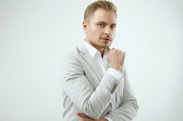 Handsome blonde man model in a fashion gray suit in studio