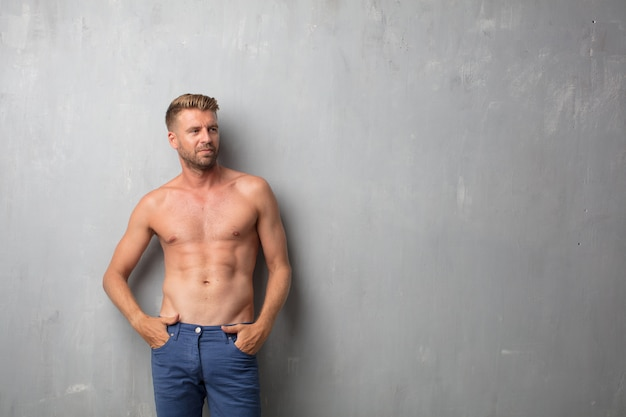 Handsome blonde man and nude torso over a grunge wall texture