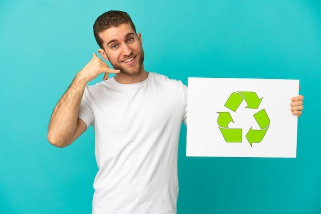 Красивый блондин на изолированном синем фоне держит плакат со значком корзины и делает жест по телефону