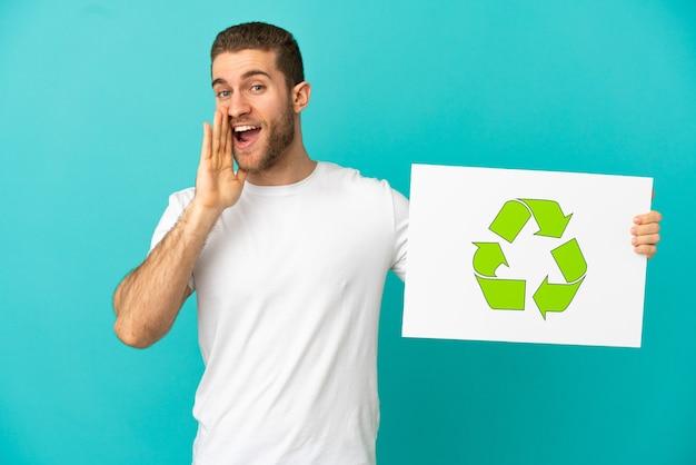 Красивый блондин на изолированном синем фоне держит плакат со значком корзины и кричит