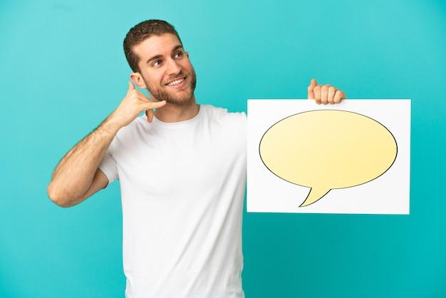 Красивый блондин на изолированном синем фоне держит плакат со значком речевого пузыря и делает жест телефона