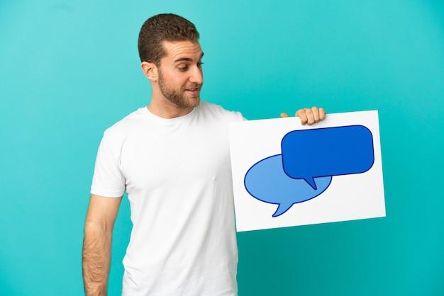 Красивый блондин на изолированном синем фоне, держащий плакат со значком речевого пузыря