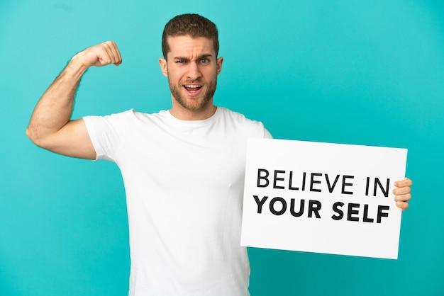 Красивый блондин на изолированном синем фоне держит плакат с текстом «верь в себя» и делает сильный жест