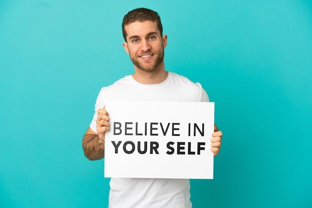 격리된 파란색 배경 위에 있는 잘생긴 금발 남자는 행복한 표정으로 자신을 믿으라는 문구가 적힌 플래카드를 들고 있습니다.