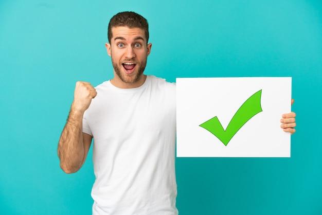 텍스트 녹색 확인 표시 아이콘 및 축하 승리와 현수막을 들고 고립 된 파란색 배경 위에 잘 생긴 금발의 남자