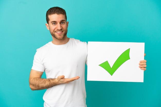 Красивый блондин на изолированном синем фоне держит плакат с текстом зеленой галочки и указывает на него
