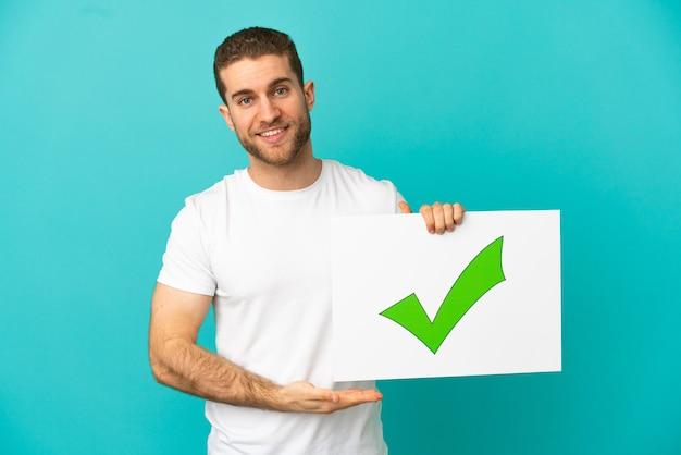 행복 한 표정으로 텍스트 녹색 확인 표시 아이콘으로 현수막을 들고 고립 된 파란색 배경 위에 잘 생긴 금발의 남자