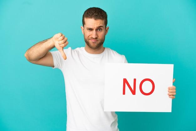 외진 파란색 배경 위에 아니오라는 문구가 적힌 플래카드를 들고 나쁜 신호를 하고 있는 잘생긴 금발 남자