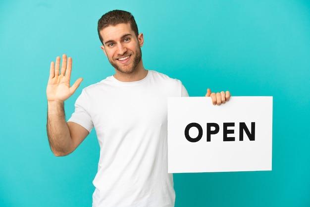 Красивый блондин на изолированном синем фоне держит плакат с текстом open и приветствует