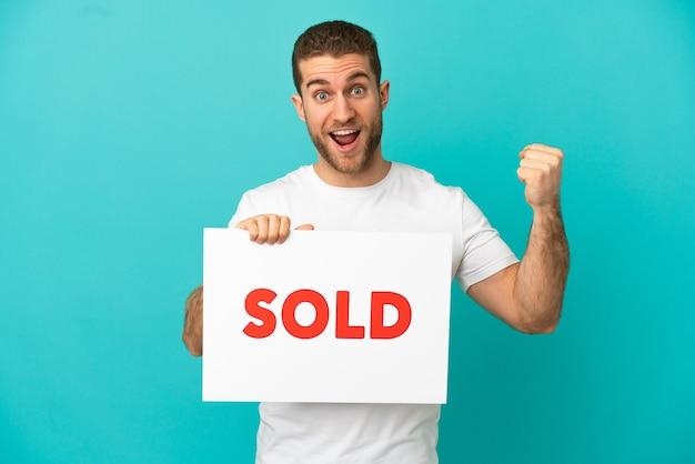 Красивый блондин на изолированном синем фоне держит плакат с текстом продано и празднует победу