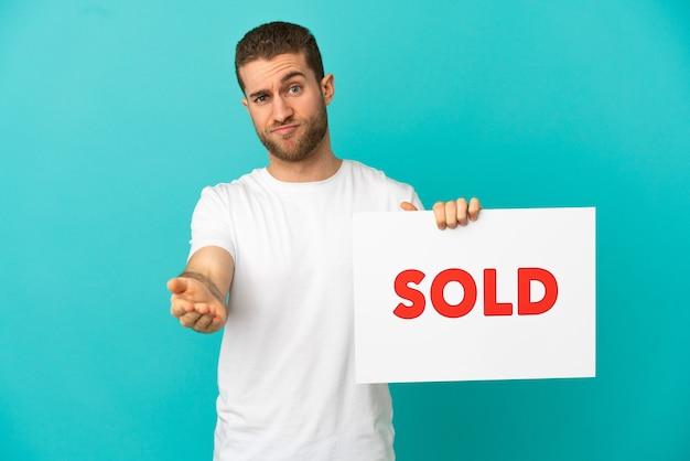 Красивый блондин на изолированном синем фоне держит плакат с текстом продано, заключая сделку