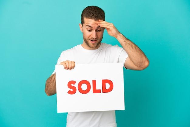 Красивый блондин на изолированном синем фоне держит плакат с текстом, проданным с удивленным выражением лица