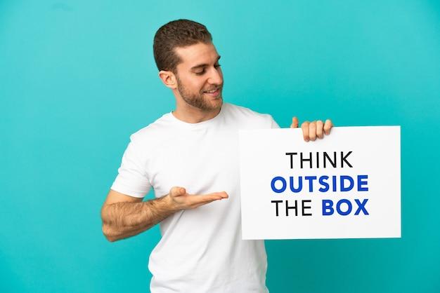 テキストのプラカードを保持している孤立した青い背景の上のハンサムなブロンドの男は、ボックスの外側を考えて、それを指しています