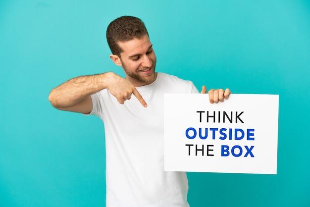Красивый блондин на изолированном синем фоне держит плакат с текстом «думай нестандартно» и указывая на него