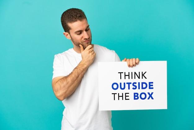 격리 된 파란색 배경 위에 잘 생긴 금발의 남자 텍스트 상자 밖에서 생각하고 생각과 현수막을 들고