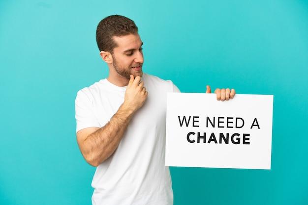 テキストとプラカードを保持している孤立した青い背景の上のハンサムなブロンドの男私たちは変更と思考が必要です