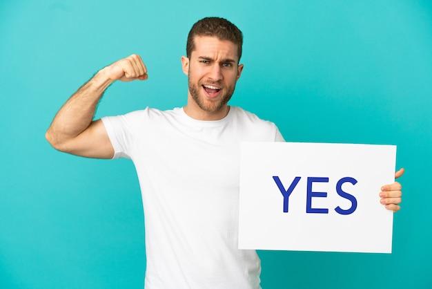 Красивый блондин на изолированном синем фоне держит плакат с текстом да, делая сильный жест