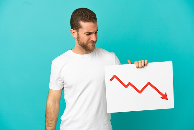슬픈 표정으로 감소하는 통계 화살표 기호가 있는 기호를 들고 고립된 파란색 배경 위에 잘 생긴 금발 남자