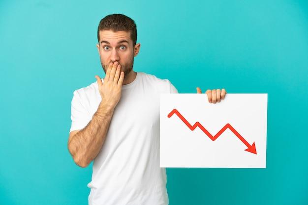 孤立した青い背景にハンサムな金髪の男が驚いた表情で減少する統計矢印記号で看板を持っている