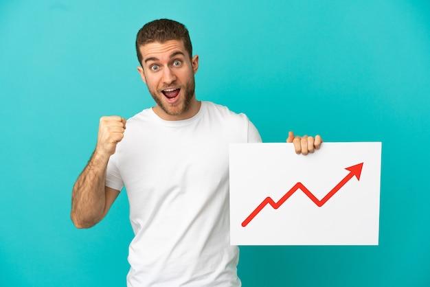 Красивый блондин на изолированном синем фоне держит табличку с растущим символом стрелки статистики и празднует победу