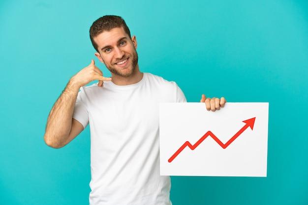 成長している統計矢印記号と電話ジェスチャーをしている看板を保持している孤立した青い背景の上のハンサムな金髪の男